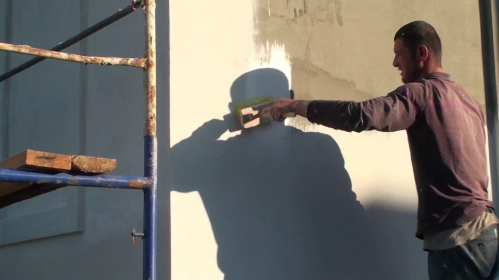 Мужчина грунтует стену