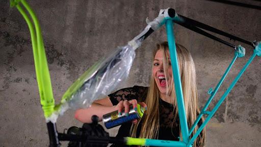 девушка красит велосипед